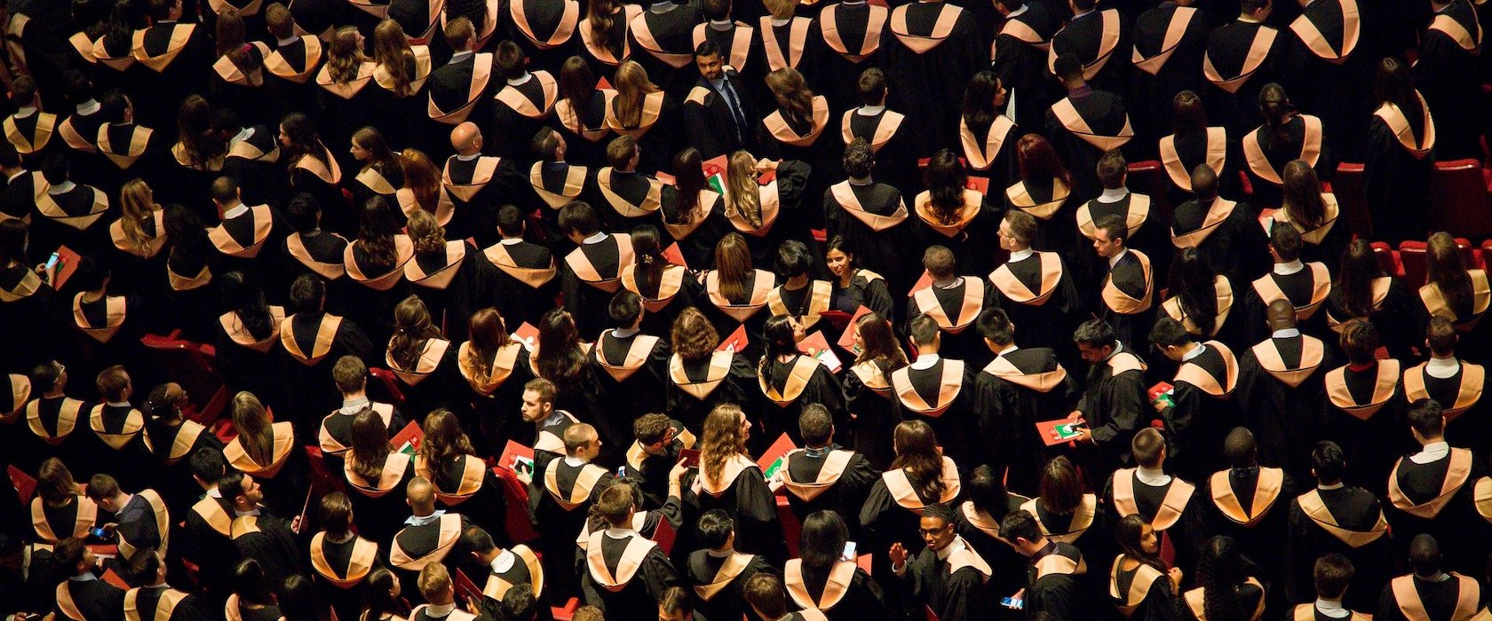An overhead view of a large group of students in graduation gowns at a ceremony