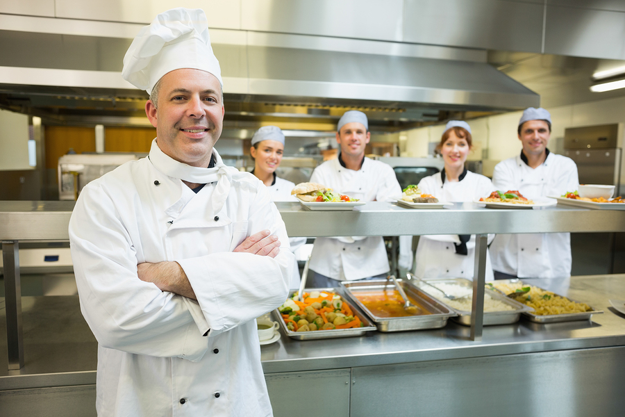 Proud mature head chef posing in a modern kitchen with his colle