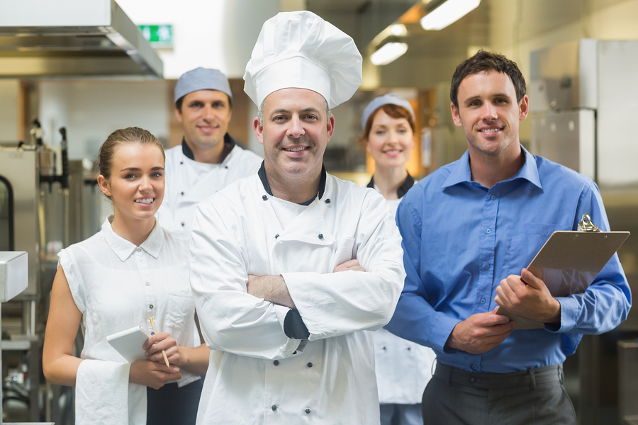 Head chef posing with the team behind him in a professional kitc