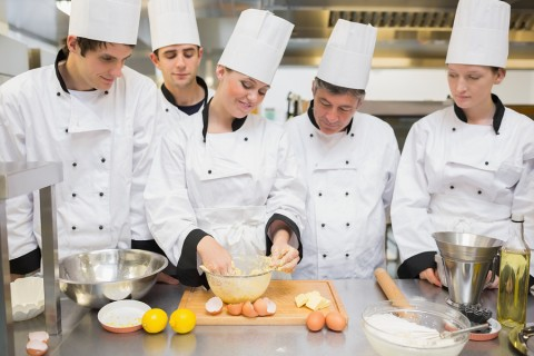 Pastry chef showing students how to prepare dough in kitchen