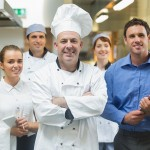 Head chef posing with the team behind him in a professional kitchen