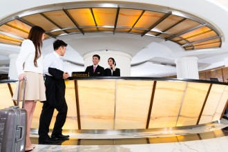 Asian Chinese woman and man arriving at front desk or reception