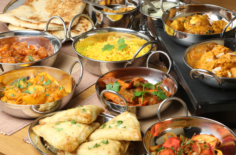 Selection of Indian food including curries, rice, samosas and na