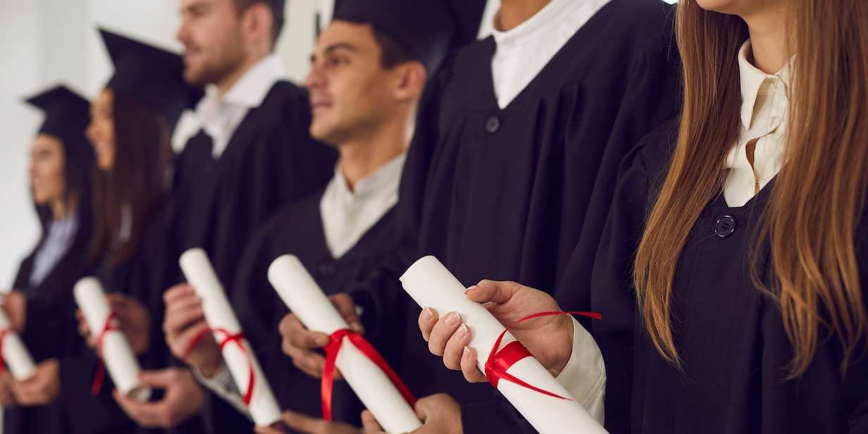 College or university students in black gowns holding traditional diploma scrolls at graduation ceremony.College or university students in black gowns holding traditional diploma scrolls at graduation ceremony.