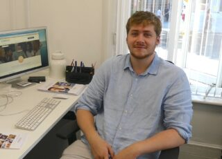Image of CTH intern, Tommy Fenwick smiling while sitting at his work desk