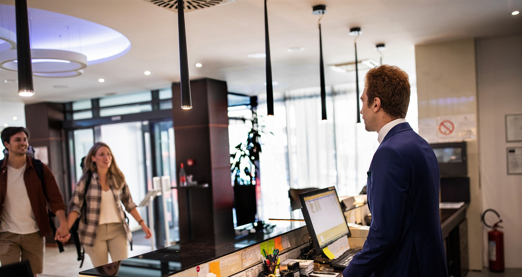 Happy young male and female couple being greeted by receptionist, as they walk to the front desk of a luxury hotel to check-in.